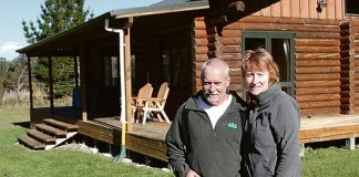 Steve Garnett and Tracey Lynch in front of a lodge on their property, close to where the fire started. Photo: Andrew Board.