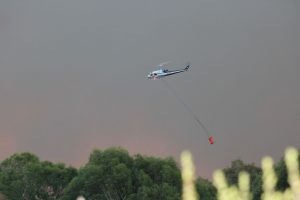 A helicopter fighting the fire near Eves Valley on Tuesday evening. Photo: Sara Hollyman.