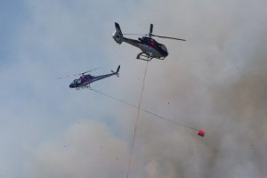 Helicopters battle the blaze. Photo: Evan Barnes